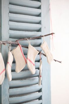antique linen sewn into little stockings hung from twig on a shutter.  makes me smile!