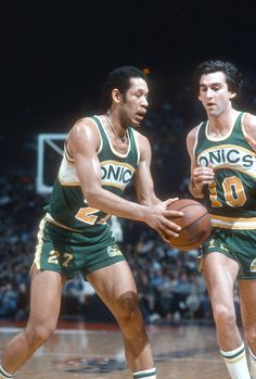 John Johnson of the Seattle Super Sonics hands the ball off to teammate Joe…