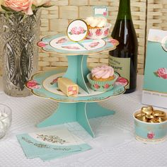 Display your cakes and sandwiches on this elegant stand from our Eternal Rose collection. Infused with classic vintage style, the two-tier stand features scalloped edges and a rose topper, with plenty of room on both tiers for a variety of sweet and savoury delicacies. Utilising an elegant colour scheme of turquoise, white and pink, the stand is finished with gold edging to add a little extra sparkle to your table.