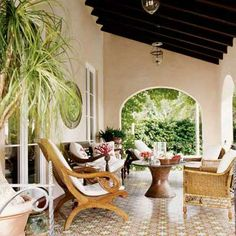 Designer Jenny Peters enlivened the terrace behind her early 20th-century Miami home with tropical influences that speak to the period. Classic British Colonial elements here are the plantation chairs, bamboo armchairs, palms & bell jar lanterns.