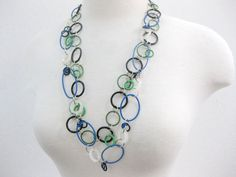 Rubber ring necklace - double strand - green,black,white rings. This is a medium length necklace using all rubber rings. the rings are varied in size and the necklace has a toggle closing. This is a wonderful summer necklace. SOOO very light weight and easy to wear. Goes with everything. I consider this to be a minimal piece, even architectual. I like my necklaces to have a clean look. Rubber is still considered to be an alternative material. I can make this piece longer or shorter, on re...