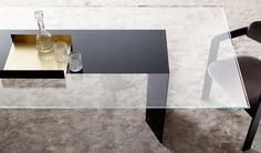 Dolm dining table with a glass top and stunning wooden base covered by painted glass. Available from IQ Furniture.