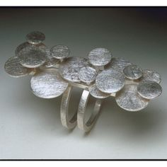 "The Bubble Ring is a dramatic piece. Various sizes of silver discs are layered to create a dynamic sculptural shape. The piece is 2 1/4"" long by 1/2"" wide. Each ring is made to order, please include y"
