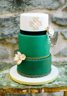 Celtic themed 3-tiered wedding cake. Bottom two tiers are emerald green, accented by gold trim and a flower. Top layer is white with gold Celtic knot hearts. From the Emerald Isle Inspired Photo Shoot from Love by Serena | Style Me Pretty