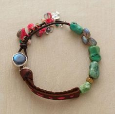 """Turquoise and labradorite nuggets set the tone for our exclusive handcrafted bracelet. Accents include sterling silver charms, pink opals and aquamarines. Approx. 7-1/2""""L."""