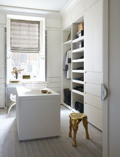 The custom closet provides plenty of open and hidden storage, as well as a vanity area with a city view | archdigest.com