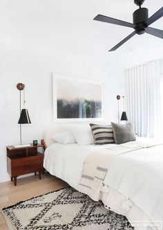 Neutral bedroom with black wall sconces, mid-century nightstand and Moroccan shag rug.
