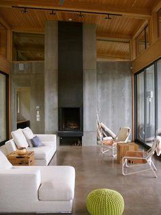 Sala com pé direito duplo com parede e piso em cimento