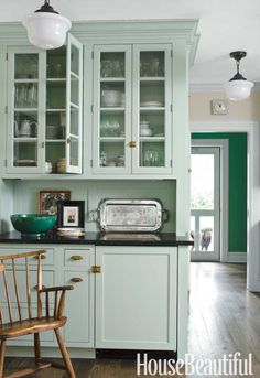 Some cabinets are glass-fronted, to display special dishes and glassware. Paint in the mudroom beyond is Farrow & Ball's Arsenic.