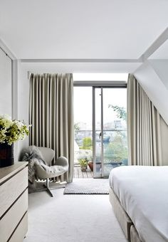 Lovely bedroom with heavy curtains, soft carpets and a color mix of beige, camel and white tones which creates a lovely atmosphere.