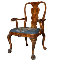 """A Georgian style carved walnut open armchair with grotesque carvings to the arms and knees with a drop in needlepoint seat ending on fury lion's paw feet. CIRCA: 1890 - 1910 DIMENSIONS: 41.5"""" h x 25.25"""" w x 21"""" d"""