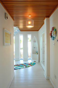 The surf board rug and boat shaped shelves add a playful touch to a coastal hallway.