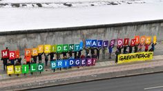 "Activists from Greenpeace display a message reading ""Mr President, walls divide. Build Bridges!"" along the Berlin wall in Berlin to coincide with the inauguration of Donald Trump as the 45th president of the United States. Photograph: John MacDougall /AFP"