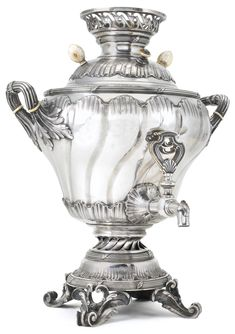 FABERGÉ~ Silver samovar, Moscow, circa 1895 of baluster form, repoussé with rocaille swirls within leaf-bound reed borders, the handles of ribbon-bound stems with acanthus leaf brackets, the circular plinth on leaf scroll feet with floral garlands, pierced cartouche-form tap, ivory insulators and knops, gilt interior, struck K.Fabergé in Cyrillic beneath the Imperial Warrant, 84 standard