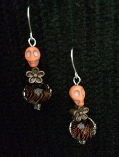 Love the tiger print bead! Perfect for Día de los Muertos! Edgy Orange Skull Earrings with Copper Flower and Tiger Bead on Etsy, $10.00