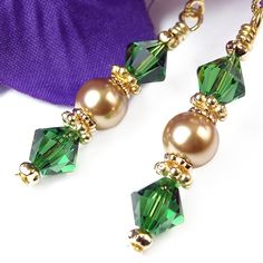 These handmade clip-on earrings feature deep green crystals and gold glass pearls in an elegant gold-tone pair of dangles for non-pierced ears. The green crystals are Swarovski bicones (made in Austri