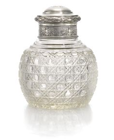 A FABERGÉ SILVER AND CUT-GLASS CANISTER, MOSCOW, 1899-1908 the body cut with faceted diaper pattern, the silver collar repoussé with swans, the domed lid engraved with Cyrillic initials GZ within a laurel border, struck K.Fabergé in Cyrillic beneath the Imperial Warrant, 84 standard.