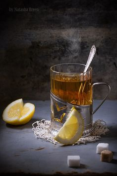Cup of Tea - Vintage glass-holder with cup of tea with sliced lemon and sugar cubes over old metal table.