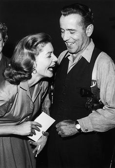 Lauren Bacall and Humphrey Bogart laughing on set between takes of the Producer's Showcase live telecast of 'The Petrified Forest', in which they both star, 1955. Photo by Darlene Hammond