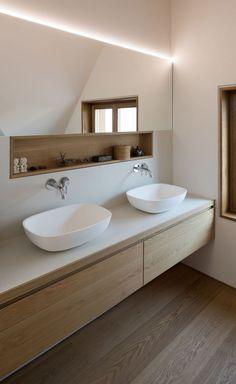 Modern Scandinavische badkamer inrichting inspiratie met zwevend hout meubel met kommen. Ook te gek; de chroom inbouw kranen en de nis waarin spullen kunnen liggen. De grote spiegel maakt het ruimtelijk. Houtlook op de vloer is te gek! Ook zo'n Scandinavische badkamer? Klik dan op de link.