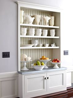 Nearby, a recessed built-in hutch stores stoneware and serving dishes without impeding foot traffic. Molding and paneling make the hutch feel authentic to the home.