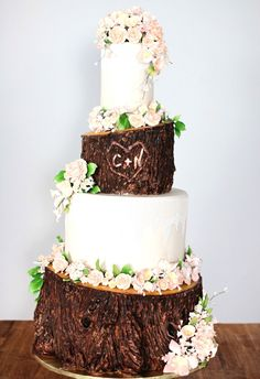 This wedding cake was inspired by nature itself. The angled cut and rough textures of the 'wood' tiers are off-set by the straight and smooth alternating tiers accented with fine and delicate sugar lace. The cake itself blossoms to life with an abundance of handmade sugar flowers dusted in subtle warm tones. It is brightened further by tiny decorative lights.