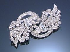 DIAMOND DOUBLE CLIP BROOCH, 1930S Each clip of radiating scroll design millegrain set with single-cut and baguette diamonds.