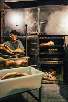 Starr Teel, owner and pitmaster, loading up the smoker!  Photo credit: Sam Dean Photography