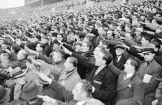 International friendly soccer match- Germany v England - Olympic Stadium - Berlin - 1938. The spectators sing the Nazi national anthem, complete with Heil salute. Note the person with the cap in lower right of the photo looking at the camera and NOT saluting or singing -- like a few others. A case for the Gestapo.