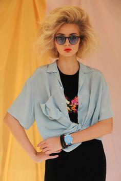80er Jahre Outfit für Frauen mit oversized Hemd in hellblau und schwarzem T Shirt mit Print, riesige Sonnenbrille, Neonlippenstift