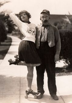 Clara Bow (age, 22) in an elephant sweater, short skirt, knee-high socks & strap-on roller-skates accompanied by comedic actor Chester Conklin (age, 41) circa 1927.