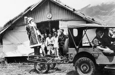 Ramu Valley, New Guinea, 1943. NX103434 Captain F. D. Smith, dressed as Father Christmas, arriving at one of the wards of the main dressing station, 2/6th Australian Field Ambulance, in a jungle cart (Thompson Stretcher), drawn by a jeep, to distribute Christmas presents to the patients. Identified personnel are: SX28258 Private E. J. Cummings; TX5952 Private R. G. Viney, and Corporal R. Roessle