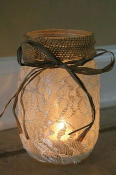 Professional-looking DIY mason jar luminary. The burlap and twine / ribbon around the top polish off the lace look. There's a tea light insight. (Maybe purple bow for my wedding centerpieces) Pot Mason Diy, Mason Jar Crafts, Diy Lace Mason Jars, Rustic Mason Jars, Wedding Mason Jars, Rustic Candles, Diy Projects With Mason Jars, Mason Jars For Weddings, Crafts With Jars