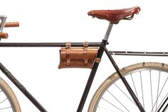 """No. 211 Bike Pouch, Tan Our bike frame pouch was modeled after a vintage one we found in France. It's perfect for your keys, wallet, phone, sunglasses or your favorite paperback. Three loops with dull nickel plated brass buckles to secure it to the frame. Collar button closures on the front flap. Adjustable. Hand-stitched with heavy wax cording. Hand-burnished and edged. 8"""" x 5"""" x 2."""" Fits a frame circumference of 3.5"""" to 5.5"""". US sourced leather.  $115.00"""