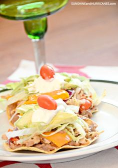 Looking for a super easy weeknight meal that the whole family will rave about? These slow cooker chicken tostados only require a few ingredients and come together for a quick meal  that will win over even the pickiest eaters. Slow Cooker Chicken Tostados. SunshineandHurricanes.com