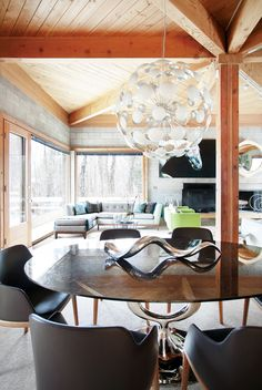 Glass chandelier above black, modern dining space, neutral L-shaped sofa with blue pillows, and cowhide rug