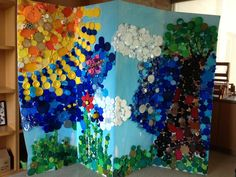 Mosaic mural made with plastic caps/tops/lids in all shapes, colors & sizes.  My Pre-K - 5th graders did this when time allowed.  I asked the staff to collect the caps, & I organized them into colors.  The kids drew a picture on a large accordion display board (which was found in the recycling pile), and then we/they worked on it after art class projects were finished.  Great time filler!