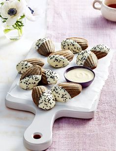 Enjoy these sweet and sophisticated black sesame madeleines     1/2 cup black sesame seeds, plus more for sprinkling     2 tbsp liquid honey     3 eggs     1/2 cup unsalted butter, melted     1/2 tsp pure vanilla extract     3/4 cup all-purpose flour     1/3 cup granulated sugar     1/3 cup ground almonds     1/4 tsp salt     75 g good-quality white chocolate, melted