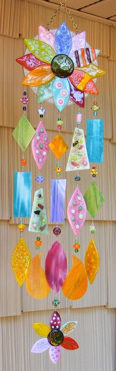 "constructed of traditional stained glass mixed with 7 fused glass pieces. All have been hand cut, drilled and strung with nylon coated stainless steel flexible wire and brass crimps. All of the beads used in the chimes are glass, some of which I have lampworked myself. The overall width of the chime is 8"" and the length is 31"" (including the hanging chain and hook). by kirksglassart on etsy"
