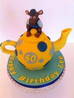 """A TEAPOT CAKE made with 5.5"""" hemisphere pans. The handle and spout are held in place using wooden skewers. The mouse is all edible and the recipient loved it. This was accompanied by 2 teacup cupcakes and an 8"""" Victoria Sponge cake with a strawberry on top. JULY 2014"""