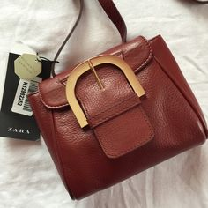 Zara Woman authentic leather bag with buckle Burgundy Zara Woman authentic leather bag with gold buckle. Buttery soft leather with a large gold buckle detail. Can be worn crossbody or on the shoulder. Straps are adjustable. There is a small scuff on the side of the bag as shown in fourth photo but is barely visible. Large enough to fit iPhone 6 Plus, a small wallet and keys. New with tags. Zara Bags Crossbody Bags