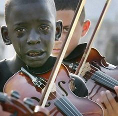 Brazilian violinist Diego Frazão Torquato weeps as he plays at the funeral of John Evandro da Silva, the teacher who introduced him to music, offering it as an escape from poverty.