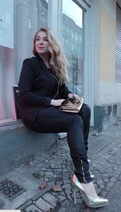 Ich trage hier eine beschichtete Hose mit Reißverschlüssen am Knöchel. Dazu trage ich ein Tanktop und darüber ein leicht transparentes, dünnes Shirt, deren Arme bis zum  Ellenbogen reichen, zusammen mit einer goldenen Körperkette, die mir schon länger gefallen hat. Schon zu den Plus-Size-Fashiondays in Hamburg, als ich mit meinen Modelkolleginnen shoppen war, habe ich sie begeistert betrachtet.