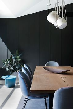 FLOS AIM pendant lights in white hang delicately in this modern dining room with minimalist decor, greenery and a wooden table.