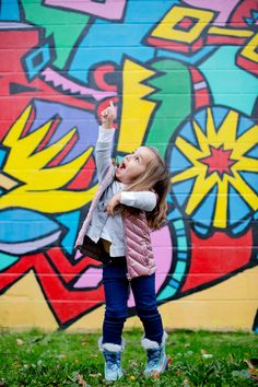 Playful portrait of a young girl (all smiles!) at a public art mural in Portland, OR. Photographed by Steadfast Studio.