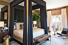 Ellen Pompeo's luxurious bedroom with grand canopy bed and antique mirror paneling.