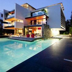 Casa contemporânea com piscina. Volumetria irregular branca, pano de vidro e sacada com acabamento preto e madeira ripada.