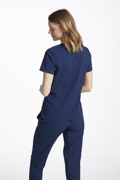 The Details: The uniquely designed Brielle V-Neck Top is a fresh take on the traditional scrub top! Shop for it exclusively at Scrubs & Beyond.  Fit/Feel: Soft stretch fabric ensures a day of comfort and flexibility.  The Clincher: Two spacious front pockets let you keep important accessories close at hand. Koi Scrubs, Lab Coats, Scrub Tops, V Neck Tops, Stretch Fabric, Fashion Forward, Flexibility, Jumpsuit, Branding