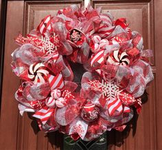 Christmas Wreath made of red silver stripe deco mesh, candy cane peppermint striped ornaments decorate as well as red white and silver ribbons.