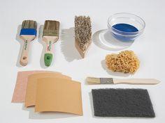 Die Werkzeuge: Beizpinsel (blau), Lasierpinsel (grün), Bürste, Kunststoff- oder Glasschale, Schwamm, kleine Flachpinsel, Schleifpapiere in verschiedenen Körnungen und Schleifvlies.